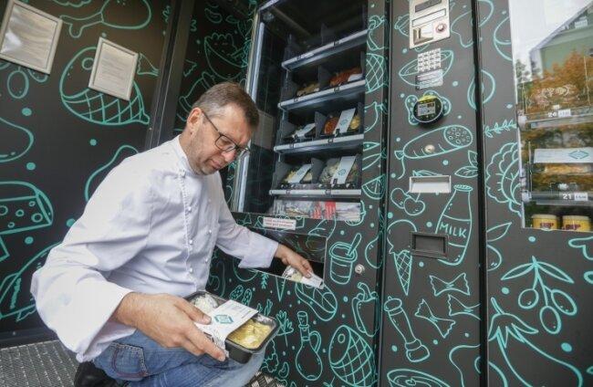 Roland Keilholz zieht fertig gekochte Gerichte aus dem Automaten. Darin liegen auch Produkte aus der Region und hochwertige Feinkost.