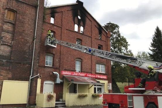 Betroffen von dem Feuer sind ein Fitness-Studio, ein Imbiss und eine Privatwohnung. Verletzt wurde niemand. Der obere Bereich des Giebels wurde inzwischen abgetragen, damit er nicht auf die B 92 stürzt.
