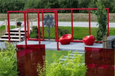 """""""Farbenspiel"""":Eine intensive rote Farbe bestimmt den Raum.Gestaltungselemente und Materialien: Pergola, Sitze und drei Glasstelen im Farbkontrast zu weißen Blüten und anthrazitfarbenen Belegen, Sitzplatz als höher gestelltes Deck mit perlgrauen Hohlkammerdielen aus recyceltem Material, keramische Terrassenplatten für die Wege im Farbton schiefer-anthrazit, ein längliches Wasserbecken und die Pergola sind aus pulverbeschichtetem Stahl, an der Pergola sind dünne Drahtseile gespannt, in einem Sternmoos-Teppich wachsen je nach Jahreszeit Tulpen, Margeriten, Sonnenhut, weiße Kletterhortensien für die Pergola und Bambus an den Stelen sowie Zieräpfel im Rasen.Ausführung: Die Gestaltung dauert zwei Wochen. Kosten: 25.000 Euro, aber variierbar. Hersteller: Weigand Landschaft GmbH Oederan"""