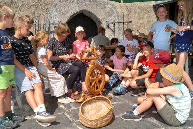 Museumpädagogin Gabriele Jenß zeigt Ferienkindern, wie ein Spinnrad funktioniert.