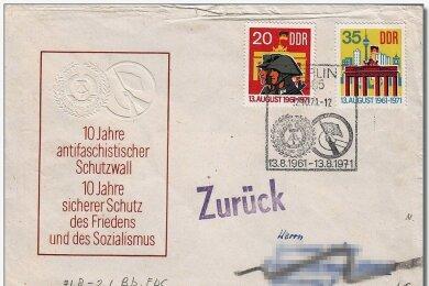 """Provokation auf dem Briefumschlag: Post aus der DDR auf dem Weg in die Bundesrepublik Deutschland war mitunter mit gestempelter Werbung für den Mauerbau versehen. Auch andere Losungen fanden sich, wie beispielsweise """"Lernt vom Sowjetvolk, lernt vom großen Stalin, wie man den Sozialismus aufbaut"""". Die Bundesrepublik reagierte in unterschiedlicher Weise darauf."""
