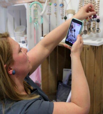 Franziska Beier ist die Inhaberin des Konzeptstores in Schwarzenberg. Über ihr Handy präsentiert sie - live auf Instagram - die Produkte im Laden.