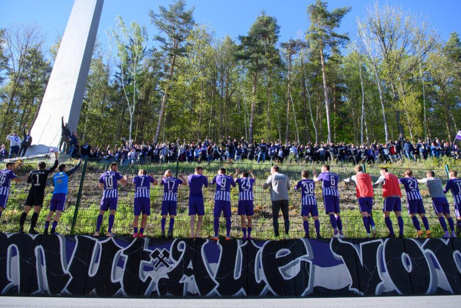 Aues Spieler feiern nach dem Spiel mit Fans, die vor dem Stadion im Wald stehen.