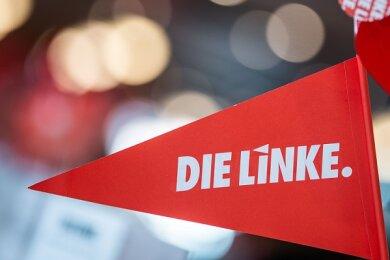 Ein Fähnchen und ein Windrand mit dem Logo der Partei Die Linke.