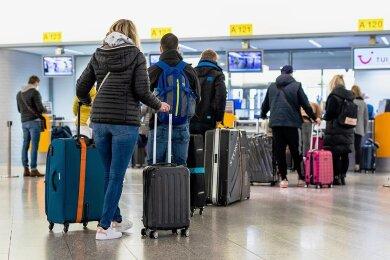 Fluggäste mit dem Reiseziel Mallorca stehen am Sonntag im Flughafen Hannover am Check-in. Von Hannover aus fliegt Deutschlands größter Reisekonzern Tui nach langer Zwangspause wieder die ersten Urlauber nach Mallorca. Tui meldet kurz vor Ostern anhaltend starke Buchungen.