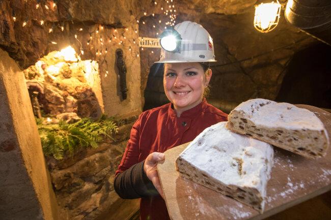 Die Konditormeisterin Anna Endter zeigt im Besucherbergwerk Finstertal in Schmalkalden (Thüringen) einen hier 30 Tage gereiften Weihnachtsstollen