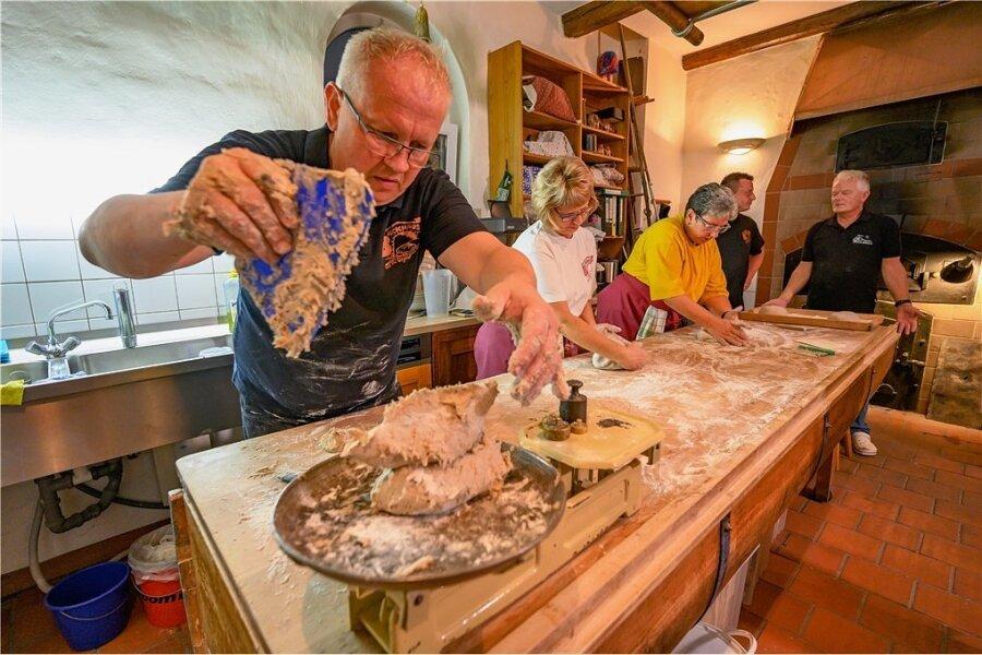 Stephan Lamm (vorn) portioniert den Teig für die Brote. Jeweils 850 Gramm hat so ein Teigling, bevor er in den Ofen geschoben wird. Nach dem Backen sind es noch um die 750 Gramm.