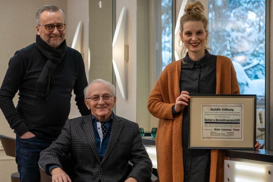 Drei Friseur-Generationen vereint: Michael Lienemann (links, 63) mit Vater Heinz Lienemann (89) und Tochter Isabel (39). Sie präsentiert die Anzeige zur Saloneröffnung von 1930.