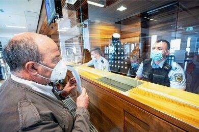 Beamte der Bundespolizei kontrollieren am Flughafen in Berlin-Schönefeld Reisende aus Sankt Petersburg, ob sie doppelt geimpft, genesen oder getestet sind. Das könnte bald für alle Reiserückkehrer gelten.
