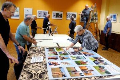 """Aufbaumarathon im Bürgerhaus: Mitglieder des Fotoclubs 78 bauten ihre aktuelle Fotoausstellung """"Vielfalt 2.0"""" auf und aktualisierten ihre Foyertafel mit Bildern das Fotoworkshops """"Outdoor-Porträts""""."""
