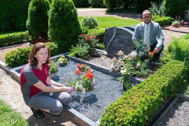 Bestatter Andreas Kohls und Ines Kästner, Mitarbeiterin für Grabpflege, an der Grabstätte auf dem Rochlitzer Friedhof, an der sich Diebe zu schaffen machten.