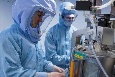 Mit Ganzkörper-Schutzanzügen simulieren Laborantinnen der Firma Biontech in einem Reinraum am neuen Produktionsstandort in Marburg die letzten Arbeitsschritte zur Herstellung des Corona-Impfstoffes an einem Bioreaktor.