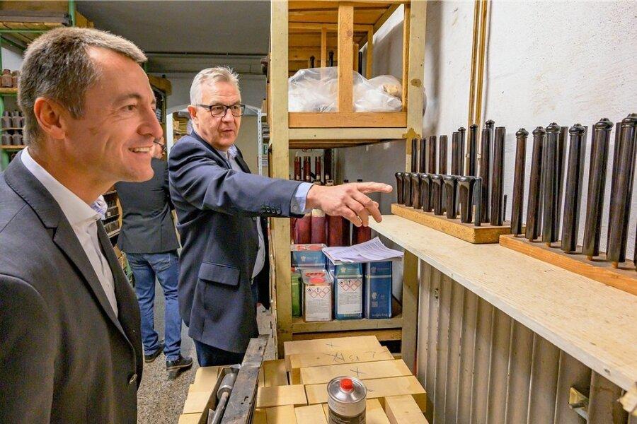 Besuchstour im Vogtland: Veit Schindler, Geschäftsführer der Gebrüder Mönnig Holzblasinstrumente GmbH, erklärt dem sächsischen FDP-Spitzenkandidaten Torsten Herbst (vorn) die Produktionsschritte.
