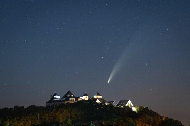 """Ein Naturspektakel können Sternengucker derzeit mit bloßem Auge erleben: Die kommenden Nächte ist der Komet namens Neowise in nördlicher Richtung stets gegen 23 Uhr mit bloßem Auge zu erkennen. Fotograf Christoph Schaarschmidt hat ihn am Samstagabend über Schloss Augustusburg gesichtet und mit der Kamera festgehalten. Der Komet Neowise, benannt nach dem US-Weltraumteleskop Neowise, nähert sich derzeit der Erde und ist deshalb gut zu erkennen. Er steht im Sternbild Großer Bär, auch Großer Wagen genannt, und ist an seinem Schweif zu erkennen. """"Er ist vor über vier Milliarden Jahren entstanden und wird uns erst in etwa 7000 Jahren wieder besuchen"""", erklärt Günter Stein von der Interessengemeinschaft Sterngucker der Sternwarte im Teichcamp Großhartmannsdorf."""