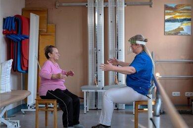 Physiotherapeutin Silvana Mohr von der Fachklinik für Geriatrie in Radeburg motiviert Gisela Druschke, ihren Brustkorb noch etwas mehr zu dehnen. Die 82-jährige Patientin hat eine Corona-Infektion überstanden.