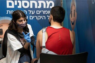 In Israel sind die Booster-Impfungen gegen Corona in vollem Gang - auch für Jüngere. Eine medizinische Angestellte in Jerusalem verabreicht einem Mann eine dritte Dosis.