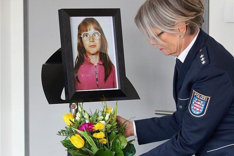 Vor der Pressekonferenz in Jena stellt eine Polizistin Blumen unter das Foto des Mädchens, das 1991 ermordet wurde.