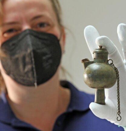 Ein alte kleine Grubenlampe hält Rebecca Wegener vom Landesamt für Archäologie in ihren behandschuhten Händen. Ein seltener Fund, der bislang der Öffentlichkeit verborgen geblieben war.