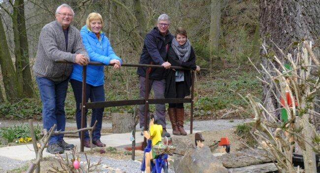 Erbauerstolz. Die Brückenbauer Birgit und Uli Kober (links) sowie Katrin Baumgärtel und Jörg Matthes am von Uli Kober gebauten und mittels Wasserrad vom Bachwasser bewegten Figuren-Ensemble.