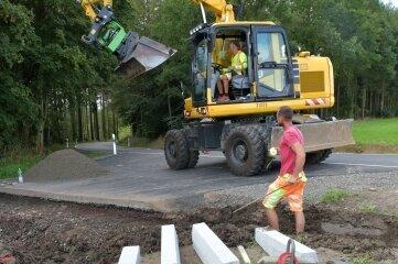 Mitarbeiter der Firma Chemnitzer Verkehrsbau bereiten das Setzen von Granitborden vor. Diese sollen in Abschlägen das Wasser aus dem Straßengraben in den Wald ableiten.