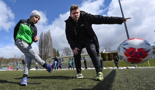 Endlich wieder gegen den Ball treten: Trainer Thomas Wels übt mit Theo,einem der Teilnehmer des etwas anderen Fußballcamps.
