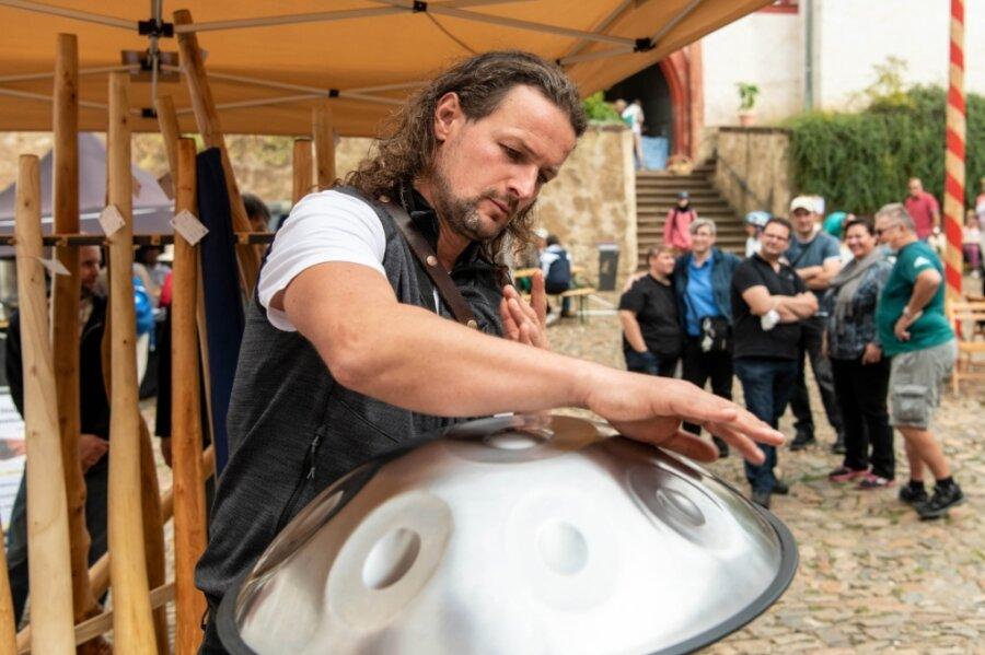 Campana-Festival auf Schloss Rochsburg: Thomas Plum vom Klangnetzwerk spielt an einem Präsentationsstand Handpan.