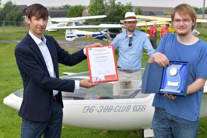 Dirk Helbig (l.) aus dem Sparkassenvorstand übergibt Michael Aßmann (r.) den Ehrenamtspreis aus dem Jahr 2020.