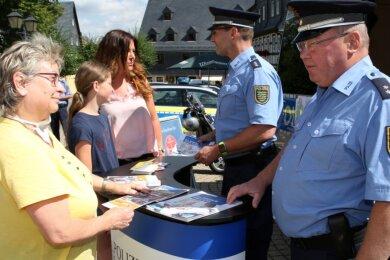 Polizeioberkommissar Martin Babst (vorn) und Polizeihauptkommissar Holger Hänsch sind auf dem Zwönitzer Markt mit Anja Becher und Tochter Helena sowie Petra Reichenauer im Gespräch.