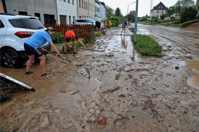 Kampf dem Schlamm: Nur zehn Minuten hatte es Anwohnern zufolge gedauert, bis sintflutartige Regenfälle am Samstagnachmittag den kleinen Dittrichbach an der Forststraße bei Meerane zum Überlaufen brachten. Schon kurz nach dem Unwetter begann das Reinemachen.