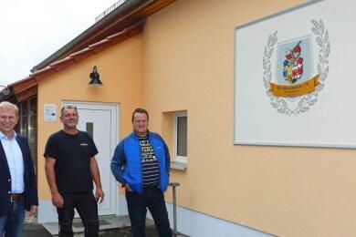 Crimmitschaus Oberbürgermeister André Raphael steht mit Karsten Egg und Dirk Michel (v. l.) vom Mannichswalder Heimatverein vor der neugestalteten Fassade des ehemaligen Jugendklubs.