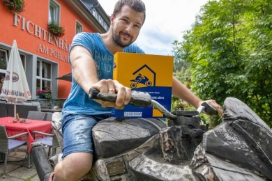 """Benny Langer auf einem besonderen Bike, das mittels Kettensäge aus einem Holzstamm geschnitten ist. Mit dabei: der Katalog des ADAC, der das Fichtenhäusel als """"motorradfreundlichen Hotelbetrieb"""" zertifiziert."""
