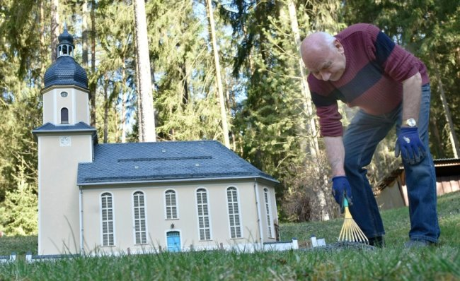 In der Miniaturschauanlage Klein-Vogtland in Adorf sorgt Museumsmitarbeiter Siegfried Friedrich für Ordnung. Im Foto arbeitet er um Umfeld der Dorfkirche Geilsdorf.