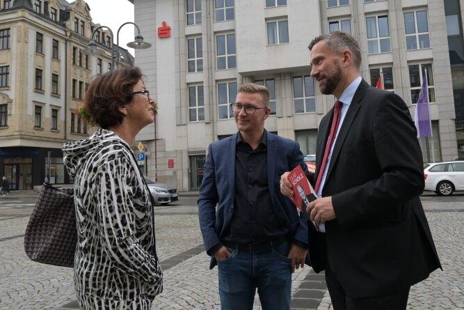 Silvio Heider (Mitte) und Martin Dulig im Gespräch mit Standbesucherin Monika Kampczyk auf dem Altmarkt in Aue.