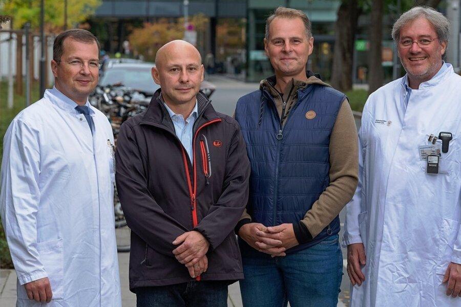 Zwei Ärzte, zwei Patienten, zwei verschiedene Therapien: Klinikdirektor Prof. Christian Thomas (l.) und Oberarzt Dr. Tobias Hölscher (r.) mit Dirk Barthel (2. v. l.) und Sven Rosentreter (2. v. r.) auf dem Gelände des Dresdner Universitätsklinikums.