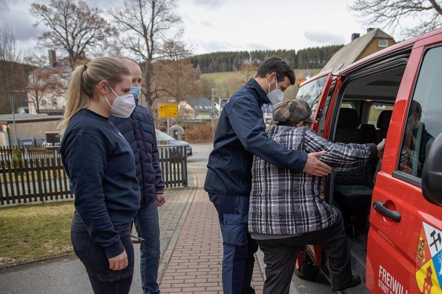 In Thum bringen Stadt, DRK und Feuerwehr Senioren auf Wunsch zum Impfen. Im Bild (v. l.): Fahrerin Johanna Neubert von der Feuerwehr Thum, Bürgermeister Thomas Mauersberger und Marc Hempelmann vom DRK-Ortsverband sowie Edith Weißer, die am Freitag mit einem Herolder Feuerwehrauto abgeholt wurde.