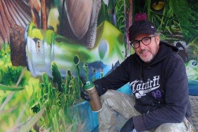 """Eine Woche hat der Graffiti-Künstler Tasso gebraucht, um eine gelbe Carportwand in diese grüne Oase zu verwandeln. Die Idee zum Motiv stammt vom Panorama """"Carolas Garten - Eine Rückkehr ins Paradies"""" von Yadegar Asisi, welches derzeit im Panometer Leipzig zu sehen ist."""