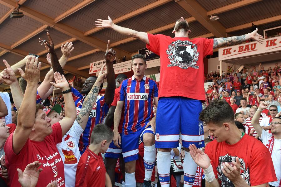 Maximilian Zimmer (oben rechts) von Energie Cottbus feiert am Sonntag mit seinen Mitspielern und den Fans den Aufstieg.
