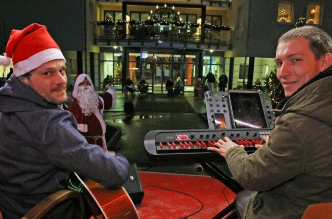 Markus Meiner (links) und Kai Dannowski sangen auf der Weihnachtsexpress-Bühne Weihnachtslieder vor dem Katharinenhof an der Wiesenaue in Reinsdorf. Und viele Bewohner stimmten mit ihnen ein.
