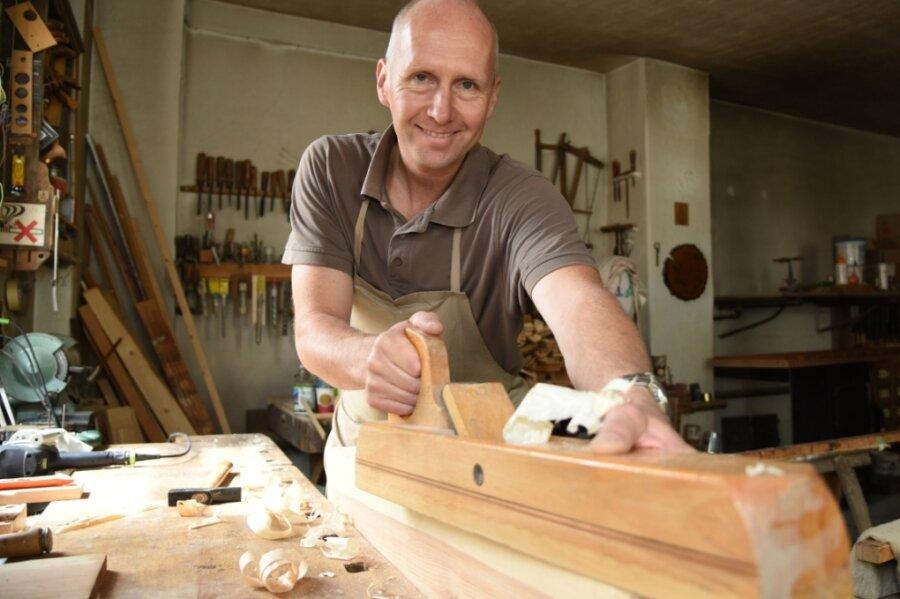 Der Oelsnitzer Tischler Jens Jacob führt sein traditionelles Familienunternehmen in Eigenregie weiter. Das Bild zeigt ihn in seiner Werkstatt beim Hobeln einer Holzoberfläche.