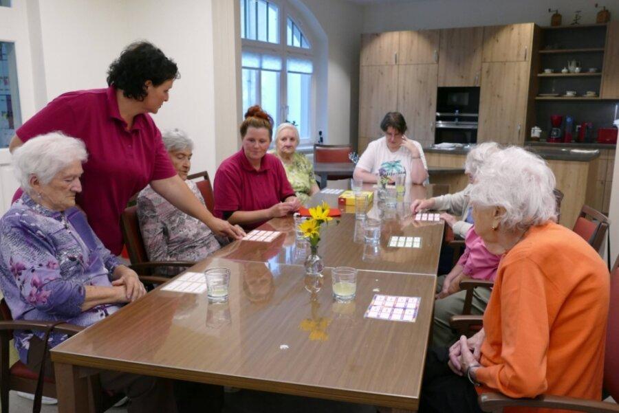 Dreh- und Angelpunkt in der neuen Tagespflege ist der Gemeinschaftsraum mit Küche. Hier spielen die Pflege- und Betreuungskräfte Nancy Schmidt (2. v. l.) und Antje Wagner (4. v. l.) unter anderem mit den Gästen der Einrichtung.