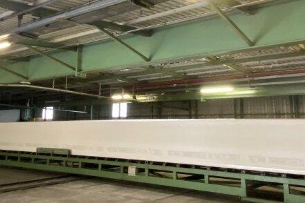Ein 27-Meter-Schaumblock verlässt die Herstellung, wird geschnitten und reift einen Tag, damit sich die kristalline Struktur festigt.