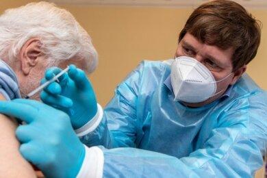 Covid-19 Impfaktion im Altenpflegeheim der SSG Rochlitz: Dr. med Martin Grzelkowski impft einen Senior in der Tagespflege.