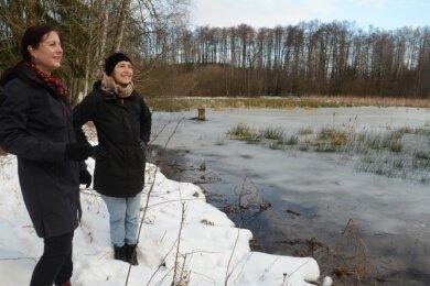 NUZ-Leiterin Antje Becker (links) und Mitarbeiterin Sarah Böhm schauen sich den Schwarzen Teich an, der saniert werden soll.