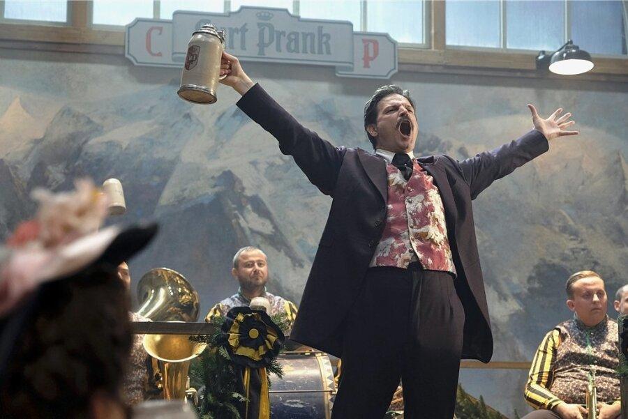 Curt Prank (Mišel Maticevic) eröffnet seine Bierburg mit 6000 Sitzplätzen und kreiert die Wiesn-Hymne.