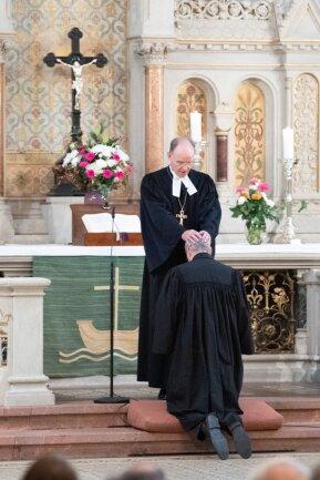 Carsten Rentzing (vorne) kniet während seiner Entpflichtung vor dem Altar in der Martin-Luther-Kirche vor Ralf Meister, Leitender Bischof der Vereinigten Evangelisch-Lutherischen Kirche Deutschlands.