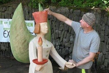 Friedhelm Schelter aus Königswalde frischt mit einem Pinsel die Farbe an seinem Engel auf.