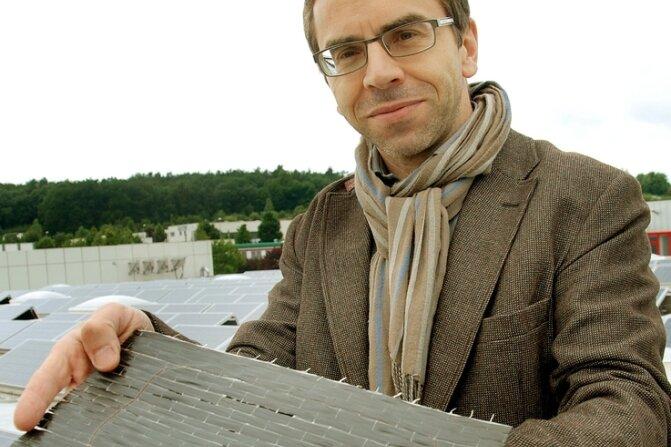Schnee-Fachmann Andreas Meybohm zeigt den Sensor im Kohlefasergewebe, der fast so aussieht wie die Fotovoltaikanlage im Hintergrund. Der Sensor wird jedoch nicht auf, sondern unter dem Dach angebracht.
