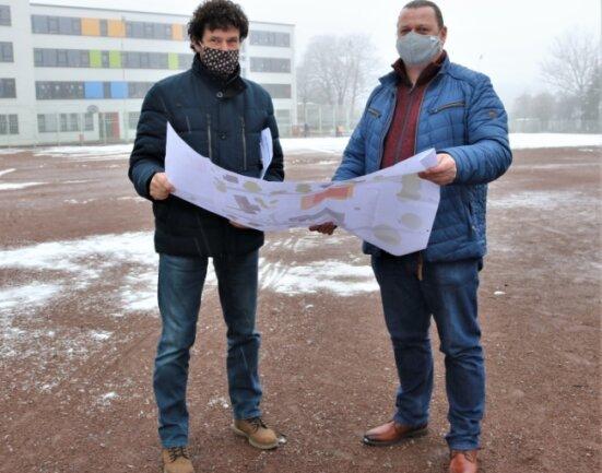 Niederwiesas Bürgermeister Raik Schubert (links) und Bauamtsleiter Lars Schuster vor der Fläche, auf der bis Ende 2023 der Sporthallen-Neubau entstehen soll.