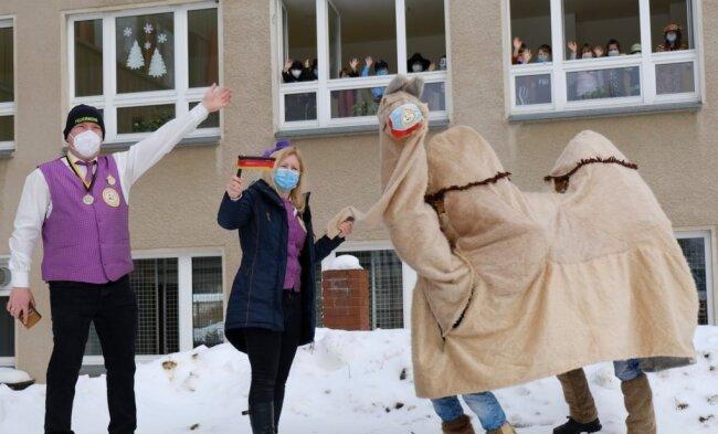Von Musik begleiteter Überraschungsauftritt des Feuerwehr-Carnevalsvereins Hauptmannsgrün vor der Grundschule. Lisette Wolf und Feuerwehrchef Andreas Müller mit Faschings-Kamel Haufaka - bejubelt von den an den Schulfenstern applaudierenden Kindern.
