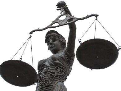 Eine Statue der Justitia mit einer Waage in ihrer Hand.